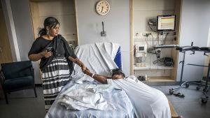 En kvinna med födslovärkar står på knä vid en säng och håller en annan kvinna i handen.