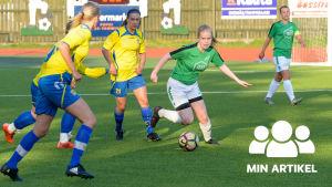 En bild på en kvinna som spelar fotboll. Hon har en grön t-skjorta. Runt henne finns motståndare i gula kläder.