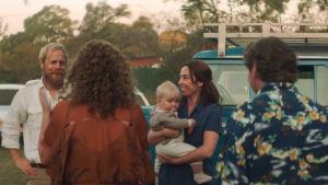 Nainen hymyilee ja pitää vauvaa sylissään, mies nauraa ja kaksi selin kameraan päin olevaa ihmistä katselee nauravaa miestä ja naista.
