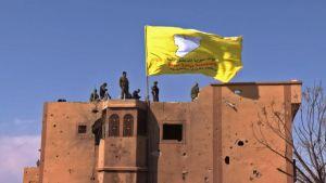 SDF reste som flagga över en byggnad i Baghouz på lördag morgon.