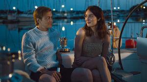Tyttö ja poika istuvat terassilla sataman pimenevässä yössä.