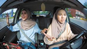 Kaksi nuorta naista autossa, toinen ratissa, toinen pelkääjän paikalla.