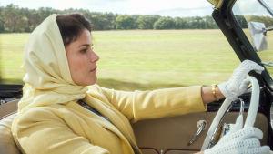 Nainen huivi päässä ajamassa autolla