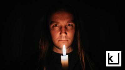 Kirjailija Mike Pohjola tuijottaa kameraan kynttilä kädessään pimeässä huoneessa.