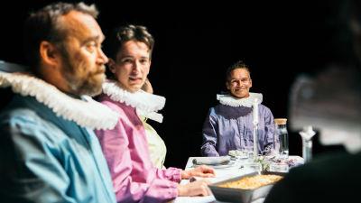 Skådespelare i färggranna kläder kring ett matbord i Unga Teaterns pjäs Fem mål mat.