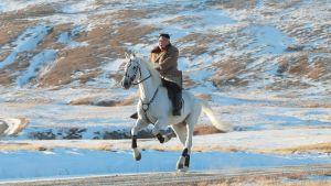 Kim Jong-un rider på en häst som rusar fram över ett snöbeklätt landskap.