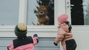 Två små barn klädda i utekläder kikar in genom ett fönster där en teddybjörn sitter.