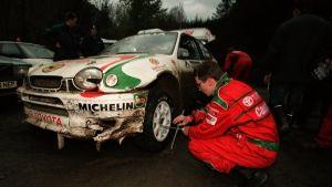 Timo Rautiainen och Marcus Grönholm byter däck på den smått demolerade rallybilen i VM-rallyt 1998 i Wales.