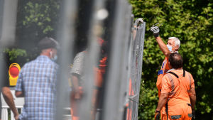 Arbetare i orange overaller bygger ett stängsel