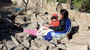 En kurdisk kvinna sitter med sitt barn ovanpå ruinerna efter hennes hus i Darbandikhan, nära Sulaymaniyah på måndagen.