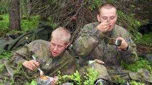 Två beväringar äter mat ute i skogen.