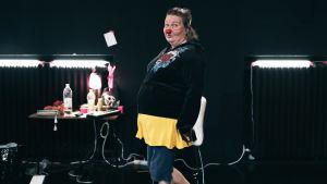 En kvinna med clownnäsa tittar in i kameran.