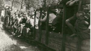 En svartvit bild på människor som åker med ett tåg.
