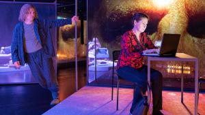 Pyjamaan pukeutunut Robin Svartström nojailee tankoon, Minna Suuronen istuu tietokoneen ääressä näytelmässä Usko, toivo, huijaus