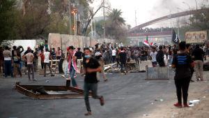 Demonstranter vid en barrikad vid lokalstyrets byggnad i Basra