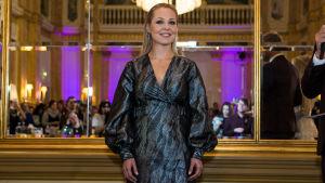 UMK-finalisti Sansa seisoo lavalla Kämpin Peilisalissa metallinhohtoisessa mekossa.