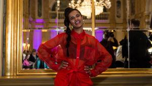 UMK-finalisti Tika poseeraa hymyillen ja kädet lanteilla punaisessa housupuvussa Kämpin Peilisalissa.