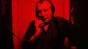 Mies pimiössä puhumassa puhelimeen.