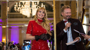 UMK-finalisti Erika Vikman hymyilee Mikko Silvennoisen haastattelussa. Vikman on pukeutunut punaiseen paljettiasuun ja Silvennoinen ruskeaan pukuun.