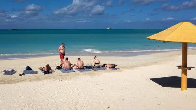 Några människor på en karibisk sandstrand, de flesta med ryggen till. Ett gult parasoll i förgrunden.