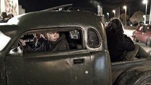 En ung pojke kör en gammal amerikansk bil, på flaket sitter en vuxen med ryggen till.