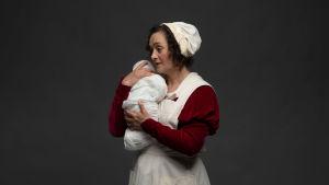 Barnmorskan håller en nyfödd baby mot sin axel. Skådespelare Nina Hukkinen.