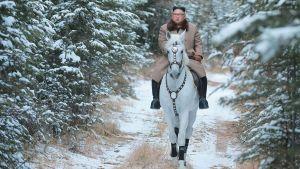 Kim Jong-un rider på en vit häst genom genom en snöig skog.