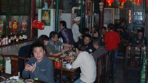 En man sitter på kinesisk restaurang med stora sällskap och servitörer i bakgrunden. Fler och fler kineser har råd att regelbundet äta på restaurang. Restaurangerna står för en oproportionerligt stor del av matavfallet.