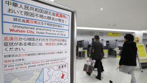 Passagerare går förbi en skylt på Narita internationella flygplats i Japan.