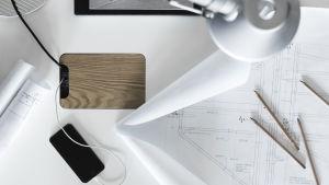 ett vitt skrivbord med ritningar, lampa ovanför