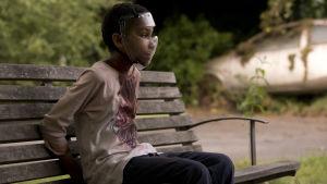 Melanie (Sennia Nanua) sitter med blodiga kläder och bakbunden med ansiktsmask på en parkbänk.