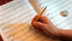 Hans skriver noter på notpapper