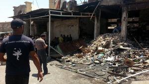 Irakier inspekterar skadorna efter armén flygräd mot Mosul 28.6.2014