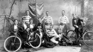Ryhmäkuva Helsingfors Velocipedklubb'in jäsenistä valokuvaamossa. KUVA Daniel Nyblin, 1800-luvun loppu.