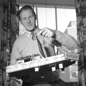 Thor Heyerdahl pitelee Kon-Tiki-lautan pienoismallia.