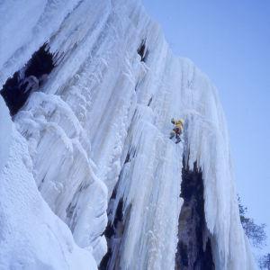 Esa Turunen näkyy pienenä hahmona kiipeämässä ylös pystysuoraa jäätikköä.