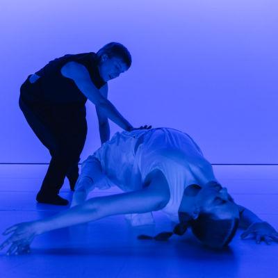 Två dansare med en blå bakgrund.
