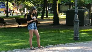 Ung flicka lyssnar på Röster ur pestens år i Gamla kyrkoparken.
