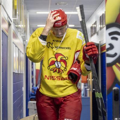 Marko Anttila går genom en korridor i hockeyutrustning.