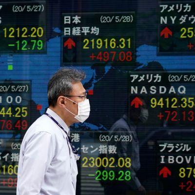 Mies kulkee pörssitaulun ohi Tokiossa. Tokion pörssikurssit ovat nousussa.