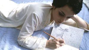 Nainen makaa sängyllä ja kirjoittaa päiväkirjaa.