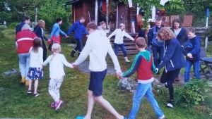 Människor som dansar i ring utomhus