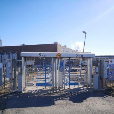 Stora Enso Veitsiluodon tehtaiden portti aurinkoisena päivänä. Taustalla näkyy punatiilisiä tehdasrakennuksia.