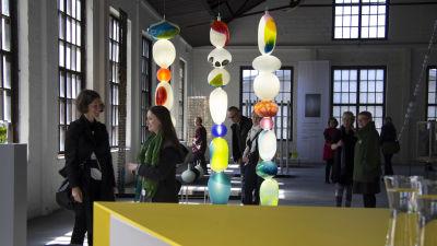 människor i utställningshall bland glaskonst