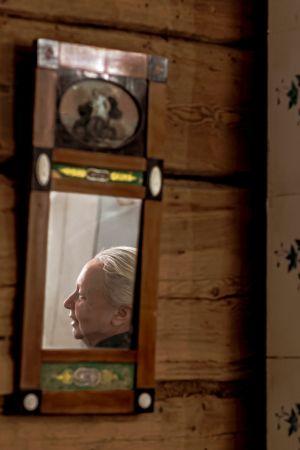 En äldre kvinna syns i profil i en liten spegel på väggen. Väggen är en brun stockväg och till höger syns en kakelugn.