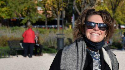 En kvinna med solglasögon ler mot kameran.