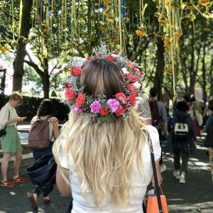 Kvinna med blomsterkrans på huvudet beundrar solrosarrangemang vid ingången till Battery Park