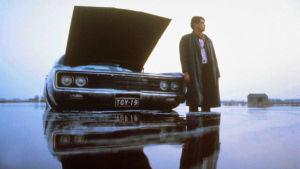 Rosso (Kari Väänänen) seisoo takki auki keskellä Pohjanmaan tulvaa, vieressä amerikanrauta  konepelti auki.