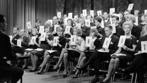 """Yleisradion televisio-ohjelma """"Ruletti pyörii Eurovision laulukilpailun merkeissä"""", Suomen loppukilpailu (Suomen karsinta). Raati antaa pisteitä kilpailukappaleille (40-jäseninen maallikkoraati, tuomaristo). Vuodelta 1963."""