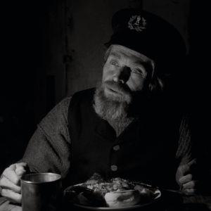 Thomas (Willem Dafoe) sitter vid bordet och äter.